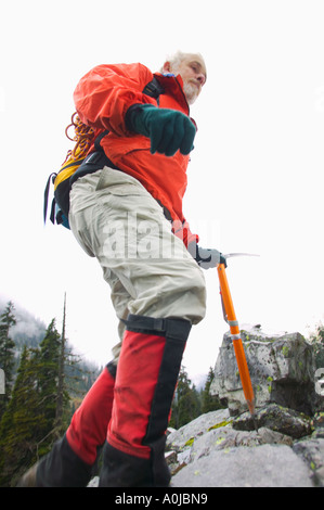 A mature man hiking on a rocky slope - Stock Photo