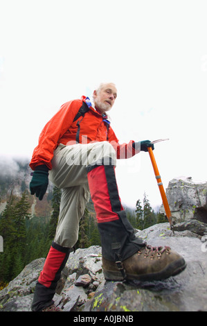 A mature man hiking on a rocky slope with a mountaineering axe. - Stock Photo