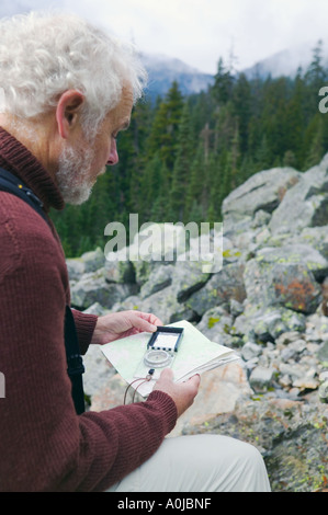 Man using a compass outdoors - Stock Photo