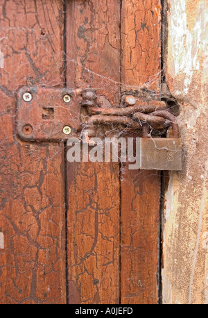 Time Lock. Rusted lock and clasp covered in cobwebs, sadly neglected - Stock Photo
