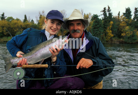 SOUTHEAST ALASKA Katmai National Park Brooks Lodge Happy Woman Fisherman and Guide Releasing Rainbow Trout in the - Stock Photo