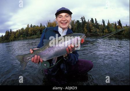 SOUTHEAST ALASKA Katmai National Park Brooks Lodge Smiling Woman Fly Fisherman Releasing Rainbow Trout in the Brooks - Stock Photo