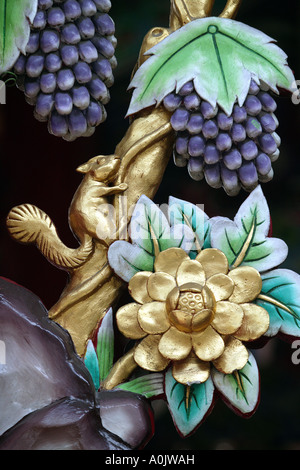 Detail of a painted carving depicting a squirrel bunches of grapes and a flower at the Wat Mangkon Kamalawat temple - Stock Photo