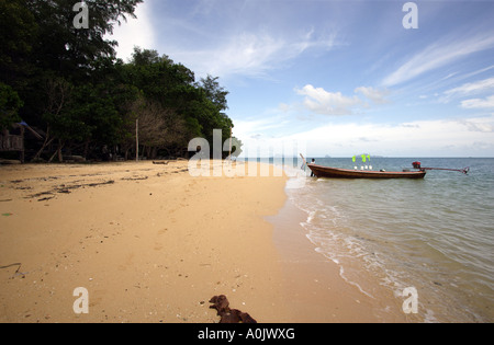 A quiet beach on the island of Bu Bu in Southern Thailand A long boat waits in the shallow water This is one of - Stock Photo