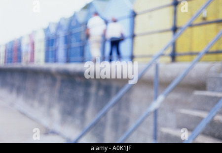 Impressionistic view from below of figures walking on seaside promenade or seawall past beach huts with steps down - Stock Photo