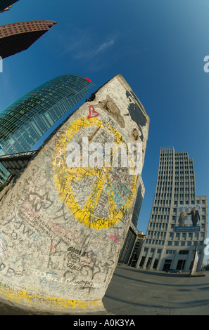 Yellow peace sign painted on a section of original Berlin Wall at the Potsdamer Platz in front of office buildings. - Stock Photo