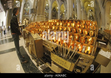 Woman and candle offering place inside St Patricks Cathedral seat of the Archbishop of New York and largest decorated - Stock Photo