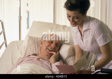 Nurse comforting recovering senior male in hospital While reading him a get well card - Stock Photo