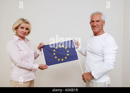 mature man and mature woman showing flag of European Union - Stock Photo
