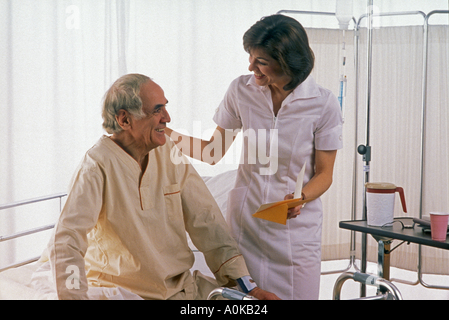 Female nurse reading get well card to a recovering patient sitting on hospital bed - Stock Photo