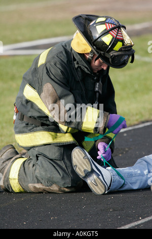 An EMT is wrapping a green colored ribbon to the leg of a victim laying on the asphalt of a school - Stock Photo