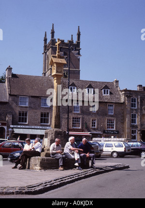 Time to sit around in the cotswold town of  Stow on the Wold next to stone cross in the market place - Stock Photo