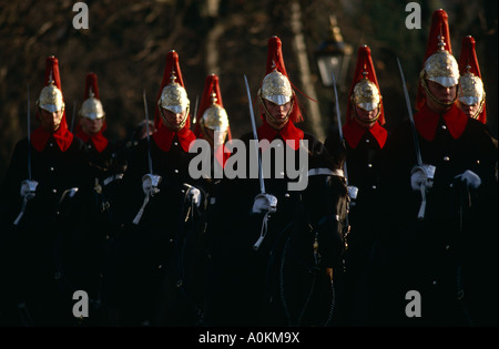 Household Cavalry ride down The Mall in London wearing winter coats going to the Changing of the Guard ceremony - Stock Photo