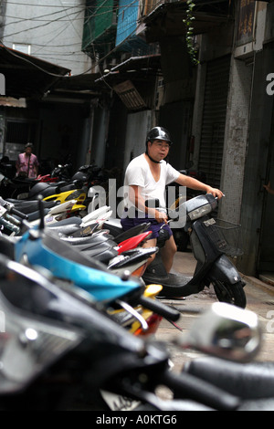 A motorbike rider pulls away from his parking space in Macau, SAR - Stock Photo