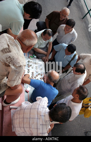 Local men gather around a game of Chinese chess in Southorn park, Wanchai, Hong Kong - Stock Photo