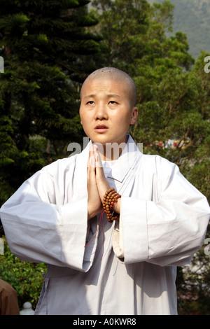 Young worshiping nun ascending ward Tian Tan Buddha, Lantau Island, Hong Kong - Stock Photo