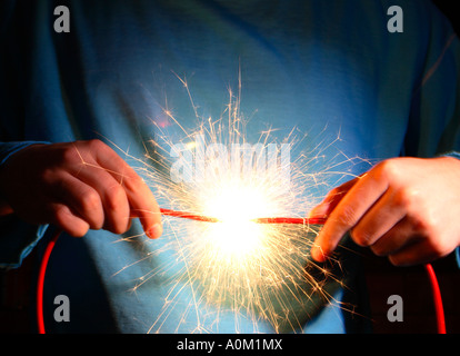 A man short circuiting two wires. - Stock Photo