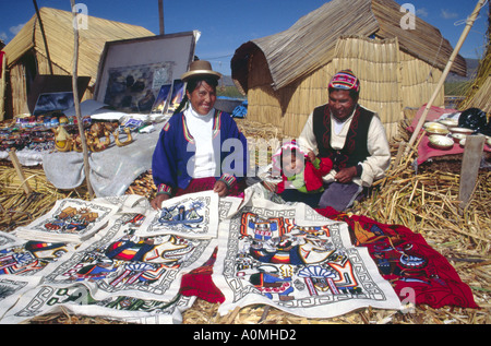 Uros family from the floating reed islands on Lake Titicaca selling colourful wall hangings in Peru - Stock Photo