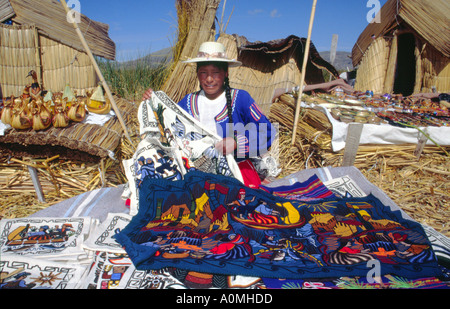 Uros woman from the floating reed islands on Lake Titicaca selling colourful wall hangings in Peru - Stock Photo