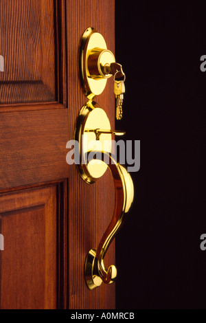 Open door with key in brass lock - Stock Photo