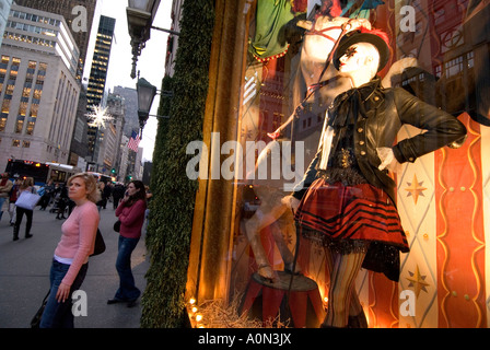 Shoppers pass Christmas window display at Bergdorf Goodman department store on 5th Avenue in Uptown Manhattan New - Stock Photo