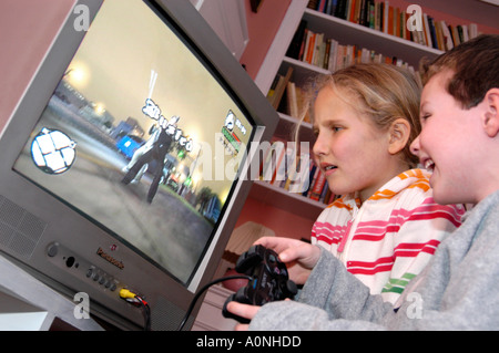 Children playing violent 18 certificate rated computer game Grand Theft Auto on Sony Playstation console, England, - Stock Photo