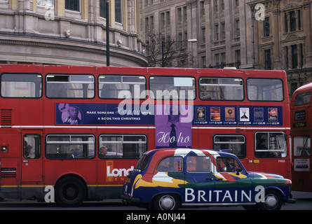 London, England, UK. Red London bus and black cab with the word 'Britain' on it. London buildings visible behind. - Stock Photo