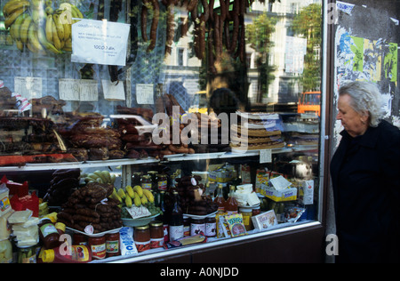 Belgrade, Serbia. Elderly woman looking at goods displayed in a shop window - sausages, bananas, cheese. - Stock Photo