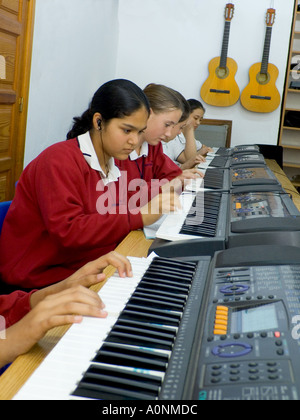 Teenage students wearing earphones practice & compose together on electronic keyboards in school music classroom - Stock Photo