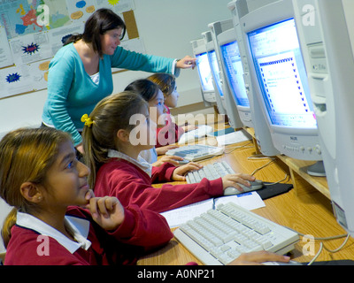 Multiracial junior girl pupils and teacher in modern school computer class room - Stock Photo