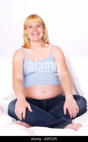 Pregnant woman sitting in bed smiling - Stock Photo