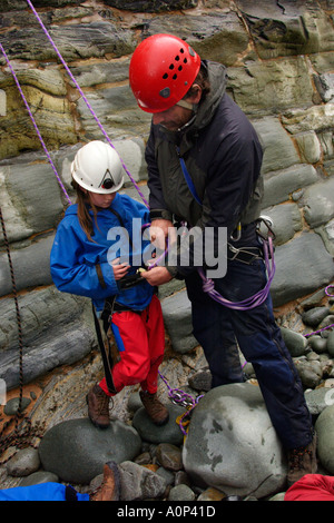 School pupils on an organised climbing expedition at Arthog Gwynedd North Wales UK GB instructor checking the safety - Stock Photo