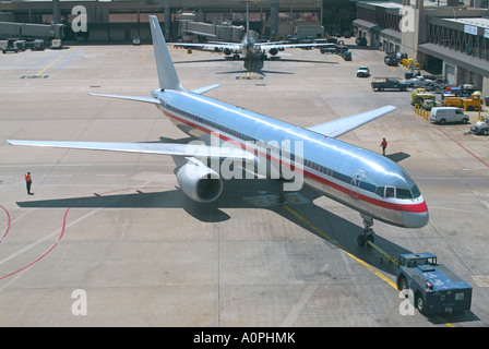 Airplane at airport gate sitting on tarmac being fueled and serviced for departure - Stock Photo