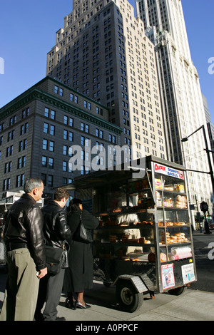 Early morning commuters in central New York City wait in line for their coffee and donut breakfast Manhattan island - Stock Photo