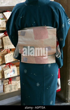 Closeup of a Japanese woman wearing traditional kimono with silk obi belt writing a religious buddhist prayer tablet - Stock Photo