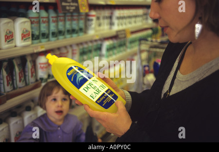 Woman examing labels on products in supermarket - Stock Photo