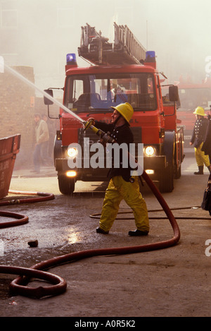 Fireman spraying water from firehose with fire engine in background. - Stock Photo
