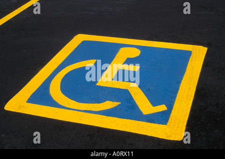 Wheelchair sign painted on parking stall indicating parking for physically challenged, disabled or handicapped. - Stock Photo