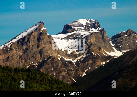 Snow tipped mountain peaks and forest in the Canadian Rocky Mountains - Stock Photo