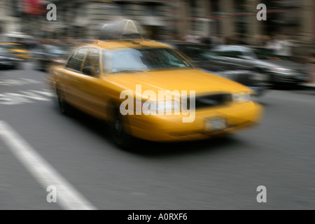Motion blurred yellow taxicab in Manhattan New York City - Stock Photo