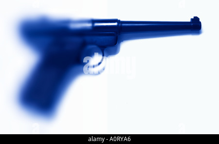 A blue tinted handgun that becomes soft blurry and out of focus on one side of the image - Stock Photo