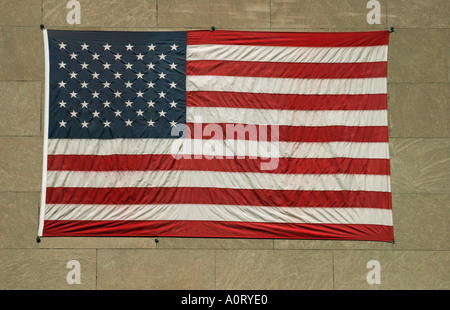 Large American flag attached to a wall on the side of a building - Stock Photo