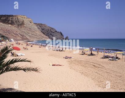 Algarve Praia Da Luz sandy beach with people sunbathing along shoreline - Stock Photo