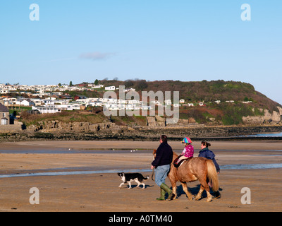 Girl on Pony and Walkers on Benllech Beach Anglesey North West Wales - Stock Photo
