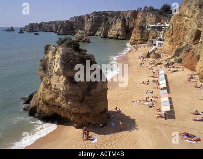 Algarve Praia Da Dona Ana sandy beach and shoreline sun shade parasoles on rocky outcrops with cliffs along coastline - Stock Photo