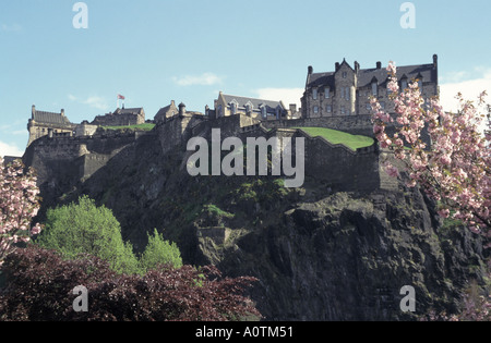 City of Edinburgh Castle with spring pink blossom on trees and union flag flying - Stock Photo