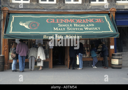 City of Edinburgh The High Street Royal Mile people window shopping at Glenmorancie malt scotch whisky store - Stock Photo