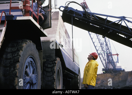 Huge coal haul truck and enormous electric dragline shovel and conveyor belt at a Texas open pit coal mine, dwarfing - Stock Photo