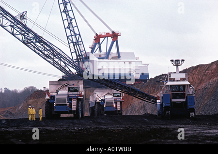 enormous electric dragline shovel and haul trucks dwarfing three workman at Texas open pit coal mine - Stock Photo
