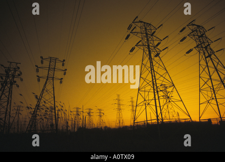 power grid showing high tension electric power transmission cables and pylons at sunset - Stock Photo